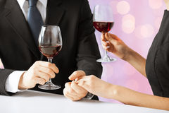 Hands of couple with diamond ring and wine glasses Stock Photography