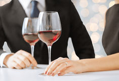 Hands of couple with diamond ring and wine glasses Stock Photo