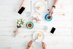 Hands of couple eating cakes and using smartphones on table. Hands of young couple eating cakes and using blank screen smartphones on wooden table with cups of Stock Photography