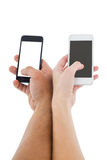 Hands of a couple holding smartphones Royalty Free Stock Image