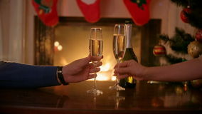 Hands of couple in love clinking glasses with champagne at Christmas eve. Man and woman sitting at burning fireplace at decorated stock video footage