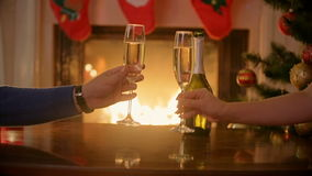 Hands of couple in love clinking glasses with champagne at Christmas eve. Man and woman sitting at burning fireplace at decorated stock footage