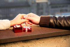 Hands of couple and open red box with golden heart Stock Photo