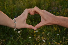 Hands couples. Men and women, forming a heart , on a background of green meadow grass and small flowers stock photos