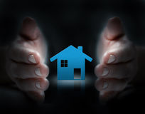 Hands cover a house. Paper cut of house icon cover by hands Stock Photography