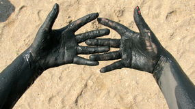 Hands covered with therapeutic wet mud. Picture taken at Techirghiol lake. Techirghiol is a lake in Northern Dobrogea, Romania, near the town with the same name royalty free stock image