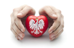 Hands covering Polish coat of arms Royalty Free Stock Photo