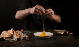 Hands cracking an egg. Man hands cracking an egg on black background Stock Photo