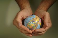 Hands cradle small globe. Hands cradle a small globe showing Europe and North Africa Royalty Free Stock Photos