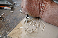 Hands of the craftsman carve a bas-relief in wood. Hands of an old craftsman carve a bas-relief in wood Stock Photo