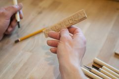 Hands of the craftsman carve with a gouge. Wood carving. Wood carving set on a wooden table. Wood chisels selection. Wooden plate with inscription. Rock royalty free stock images