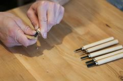 Hands of the craftsman carve with a gouge. Wood carving. Wood carving set on a wooden table. Wood chisels selection. Wooden plate with inscription. Rock royalty free stock photography