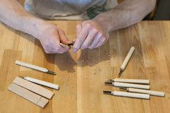 Hands of the craftsman carve with a gouge. Wood carving. Wood carving set on a wooden table. Wood chisels selection. Wooden plate with inscription. Rock stock photography