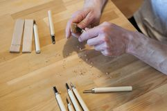 Hands of the craftsman carve with a gouge. Wood carving. Wood carving set on a wooden table. Wood chisels selection. Wooden plate with inscription. Rock stock images