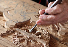 Hands of the craftsman carving Stock Photos