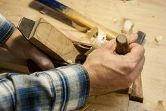 Hands of a craftsman on a old fashion woodworking plane. Planing strait Stock Images