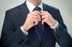 Hands & cravat. Businessman dressed up the knot of his cravat Stock Images