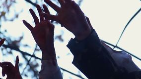 Hands of crazy monsters shaking in air, scary nightmare, mass zombie attack
