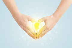 Hands creating a form with light bulb Royalty Free Stock Photos