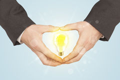 Hands creating a form with light bulb Royalty Free Stock Images