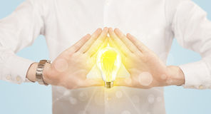 Hands creating a form with light bulb Royalty Free Stock Image