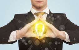 Hands creating a form with light bulb Stock Images