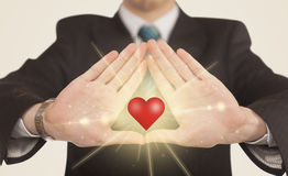 Hands creating a form with shining heart Royalty Free Stock Photos