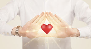Hands creating a form with shining heart Stock Images