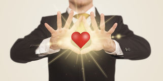 Hands creating a form with shining heart Stock Photos