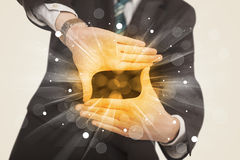 Hands creating a form with yellow shines Royalty Free Stock Photography