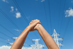 Hands crossed in assent and power transmission lines against blu Stock Images
