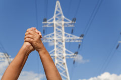 Hands crossed in assent and power transmission lines against blu. Hands crossed in assent against the background of power transmission lines and blue sky Royalty Free Stock Images