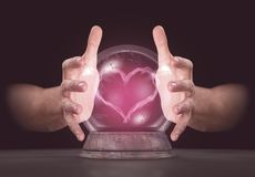 Hands On Crystal Ball. A pair of male hands surrounding a crystal ball conjuring up a pink heart shaped vapor on an isolated dark studio background Stock Photos