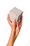 Hands and cube. Womans hands holding the concrete cube Stock Photo