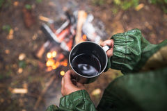 In the hands of a cup of hot tea. Person warms himself by the fire in the forest Stock Photography