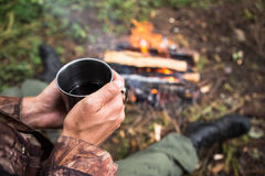 In the hands of a cup of hot tea. Person warms himself by the fire in the forest Royalty Free Stock Photo