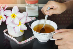 Hands with cup of tea and background of tape measures and sugar,. Diet or weight loss tea, cup of laxative tea and girl or women hand Royalty Free Stock Images