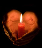 Hands cupped around a candle Stock Image