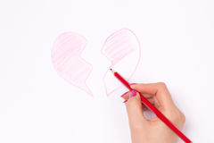 Hands, cut heart and pencil Royalty Free Stock Images