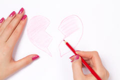 Hands, cut heart and pencil Stock Photography