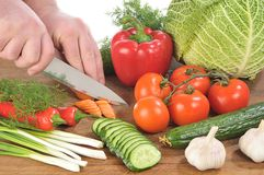 Hands cut a knife a carrot among vegetables Royalty Free Stock Photos