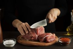 Hands cut the raw meat on wooden cutting board on dark table with seasoning and bottle of oil. Raw meat preparation in the kitchen Stock Photography