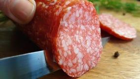 Hands cut sausage salami kitchen on a wooden background. Hands cut sausage salami a wooden background kitchen stock video footage