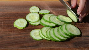 Hands cut slice cucumber knife small pieces wooden board. Female woman hands cut chop slice green ecologic cucumber in small pieces with knife on wooden board stock video footage
