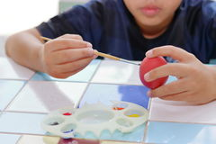 Hands of cute boy painting  egg with paintbrush for preparing Easter day. Royalty Free Stock Image