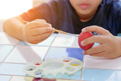 Hands of cute boy painting  egg with paintbrush for preparing Easter day. Sunshine effect Royalty Free Stock Photography