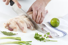 Hands cuting monkfish slices on a white background Stock Photos