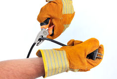 Hands cutting a cable. Hands with gloves cutting a cable with a plier isolated on white - copy space Stock Photography