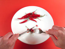 Hands cutting chili (serie). Hands slicing chilli on plate Stock Images