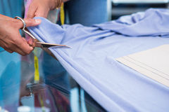 Hands cutting fabric at table Stock Photography